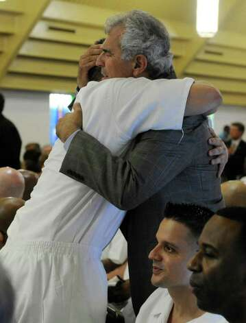 Grove Norwood, right, founder of the Heart of Texas Foundation hugs an inmate during the convocation ceremony at the Texas Department of Criminal Justice's Darrington Unit  Monday, Aug. 29, 2011, in Rosharon, Texas. Houston lawmakers and representatives of Southwestern Baptist Theological Seminary gathered to celebrate the opening of the state's first 4-year seminary program to operate entirely behind the walls of a Texas prison. (AP Photo/Pat Sullivan) Photo: Pat Sullivan, Associated Press / AP