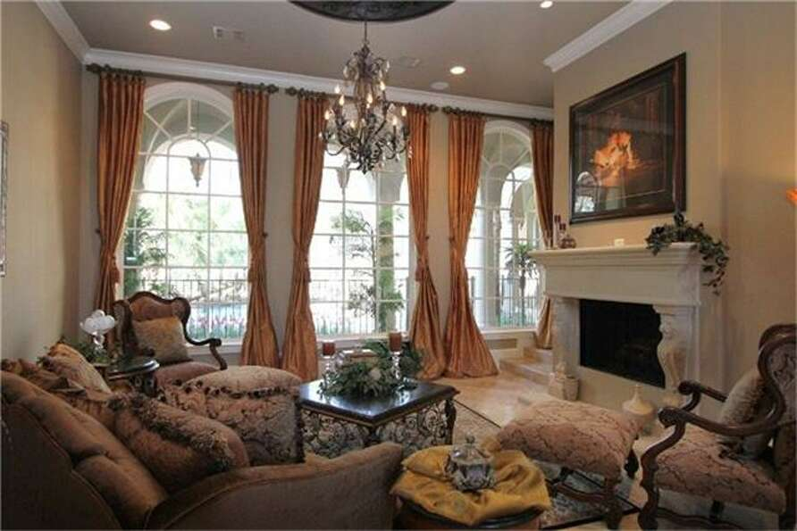 The formal living room, featuring a fireplace, an elaborate chandelier and a tremendous opportunity