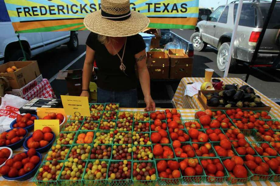 Cypress Sigman tends the produce at the Engel Farms booth on a recent  Sunday. The long growing season in Texas will keep the Quarry and some  other farmers markets open year-round. Photo: SAN ANTONIO EXPRESS-NEWS