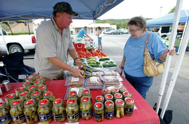 Don Hagans (left) chats with customer Sandra Swope as she buys jarred pickles at the Farmers Market at the parking lot of Leon Springs Baptist Church on Saturday, August 13, 2011. Photo: KIN MAN HUI, SAN ANTONIO EXPRESS-NEWS / San Antonio Express-News
