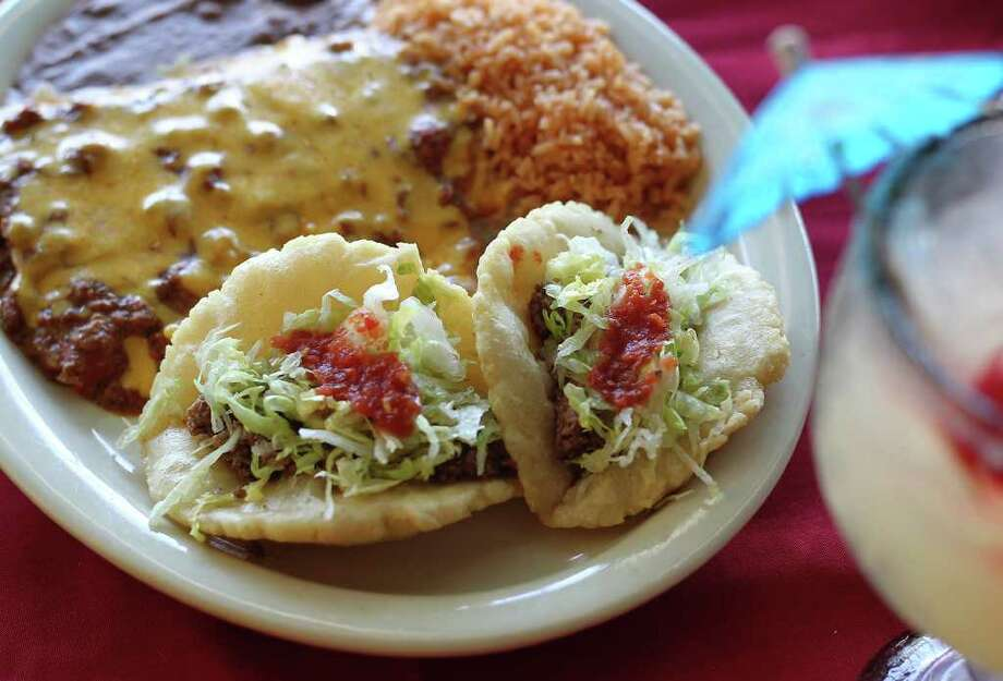 Jacala's No. 3 dinner platter comes with two beef puffy tacos, three cheese enchiladas with chili gravy, rice and refried beans. Photo: KIN MAN HUI, SAN ANTONIO EXPRESS-NEWS / San Antonio Express-News