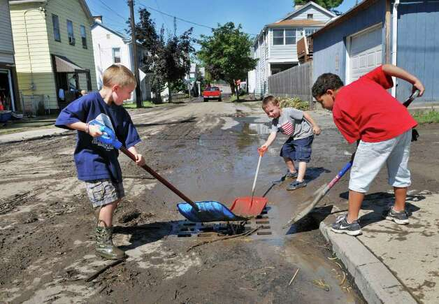 Waterford boys, from left, Benjamin Thompson, 8, Camron Thompson, 6, and Reuben Bell, 7, clean up in the aftermath of storm flooding on South Street in Waterford Tuesday Aug. 30, 2011.  (John Carl D'Annibale / Times Union) Photo: John Carl D'Annibale / 00014452A