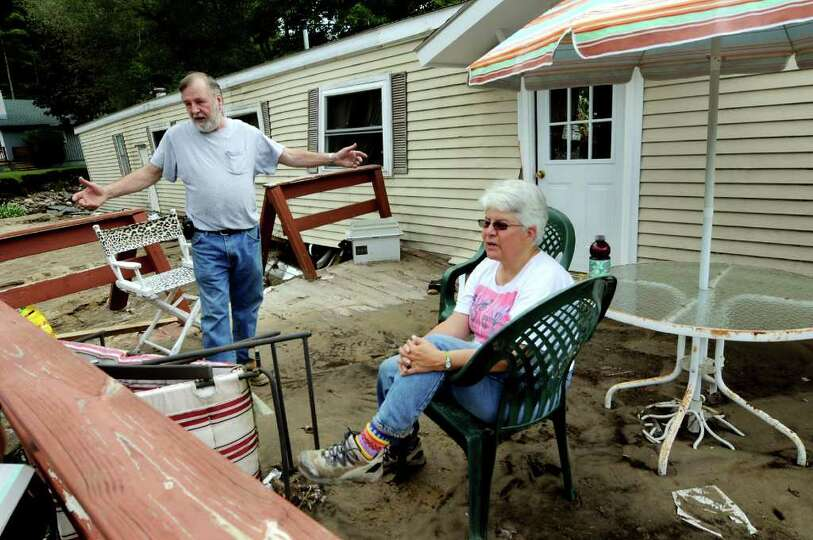 Residents Jane Martin, right, and John Hudson talk about the Gulf Brook rising and the damage to the