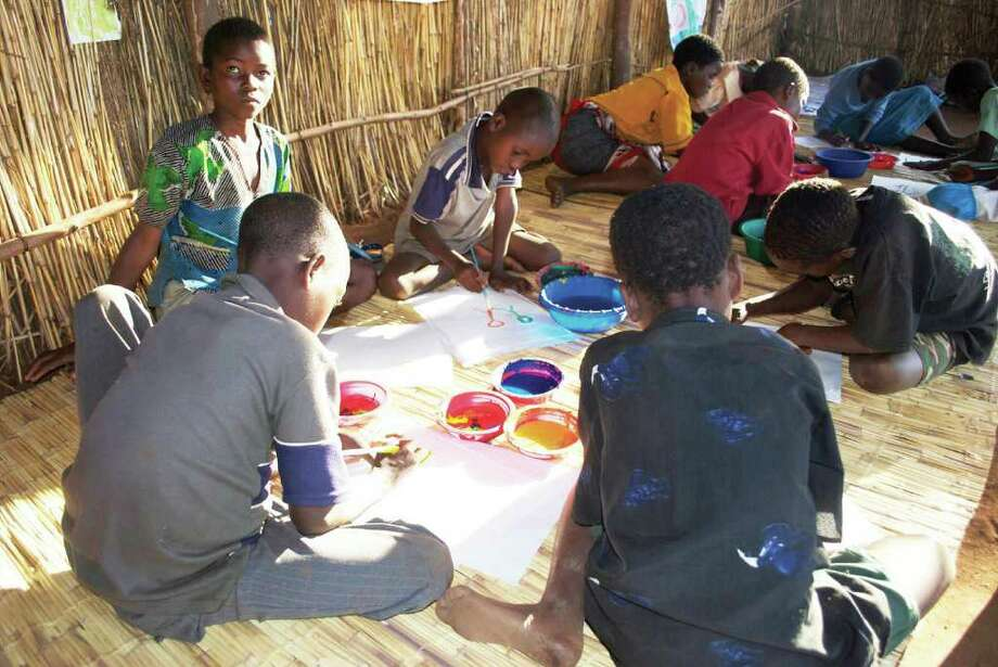 """Children in Malawi, Africa, enrolled in Save the Children's Healing and Education through the Arts program work on paintings for the Westport Arts Center's """"Malawi with Love"""" exhibit running from Sept. 16 through Nov. 6. Photo: Contributed Photo"""