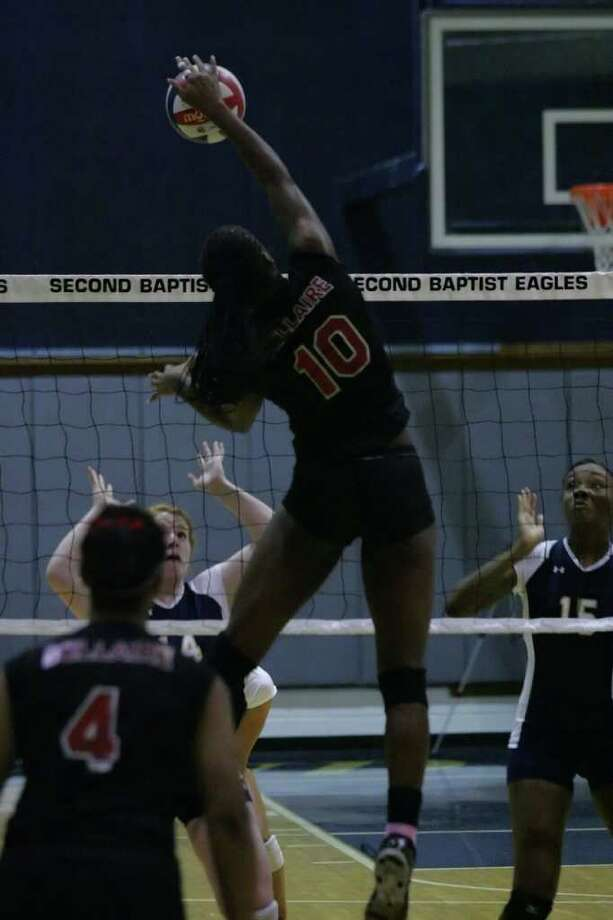 Jenelle Jordan of Bellaire spikes the ball high over the net during the Monday night match up with Second Baptist. Photo: Matthew White, Freelance / Freelance