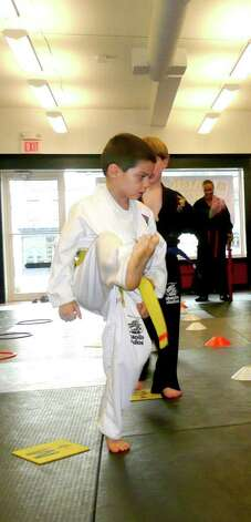 Natan Weigenfeud makes a kick in response to his sifu's command. Photo: Anne W. Semmes