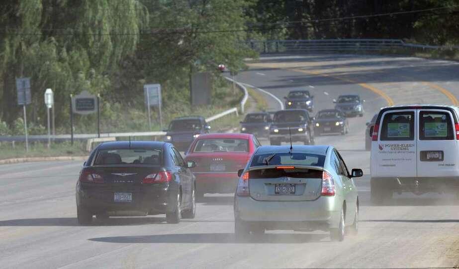 Vehicles kick up dust from dried debris on Freemans Bridge Road following Hurricane Irene, on Tuesda