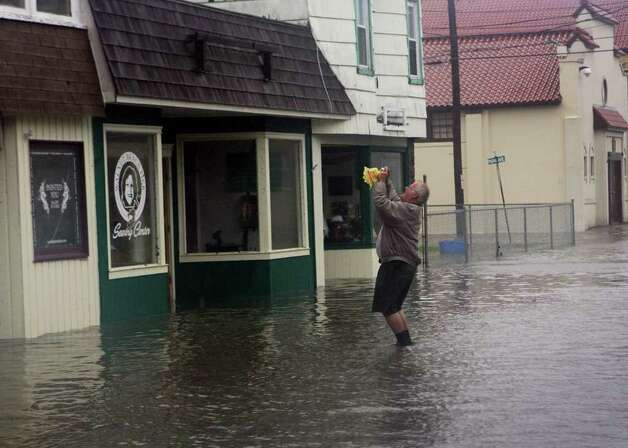 A man takes a photo in front of Walnut Beach Pier Sewing Center as Hurricane Irene weather hits Milford on Sunday August 28, 2011 and flooded the area. Photo: B.K. Angeletti / Connecticut Post