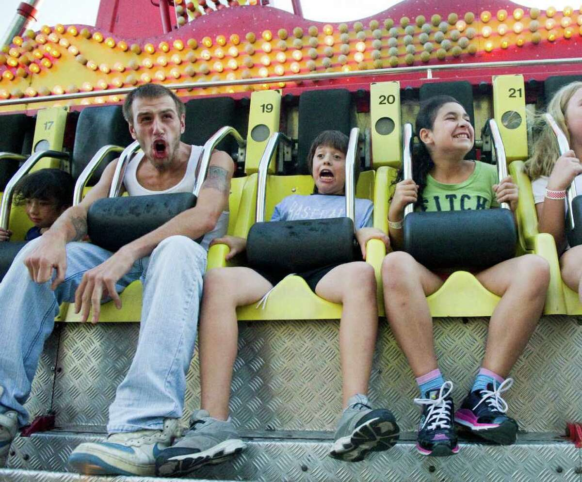 Todd Murolo, left, Pablo Mendana, 10, center, and Gianna DiMarino, 10, ride the Ali Baba as St. Leo Parish holds its 31st Annual Summer Fair in Stamford, Conn., August 29, 2011. The fair, which is free, includes international foods, live music, rides, carnival games and raffles and runs Tuesday through Friday from 6 to 11 p.m. and Saturday from 2 to 11 p.m.