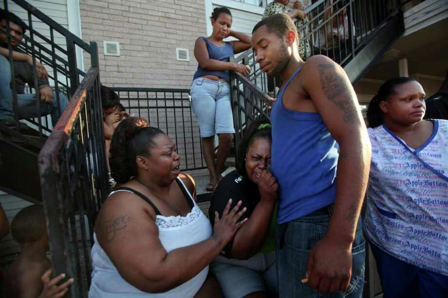 Ursella Kendrick comforts sister-in-law Yolanda Willis as she holds on to her son Miles Willis as they watch the fire department still try to extinguish fire in her building on Tuesday, Aug. 30, 2011, in Houston.  The fire broke out around 4:30 p.m. Tuesday at the Savannah at CityView Apartments on Wayforest and Richcrest near Bush Intercontinental Airport. Photo: Mayra Beltran, Staff / © 2011 Houston Chronicle