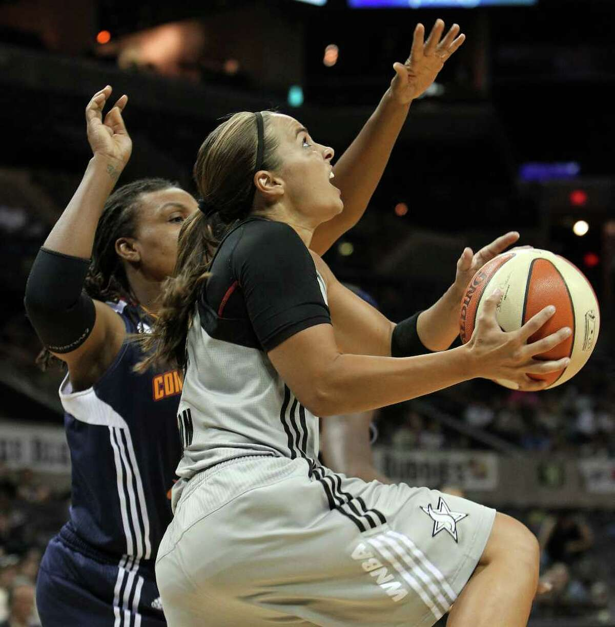 Silver Stars' Becky Hammon (25) goes up for shot to score her 4,998th and 4,999th points on her way to 5,000 points against Connecticut Suns' Tan White (14) in the first half at the AT&T Center on Tuesday, August 30, 2011. Kin Man Hui/kmhui@express-news.net