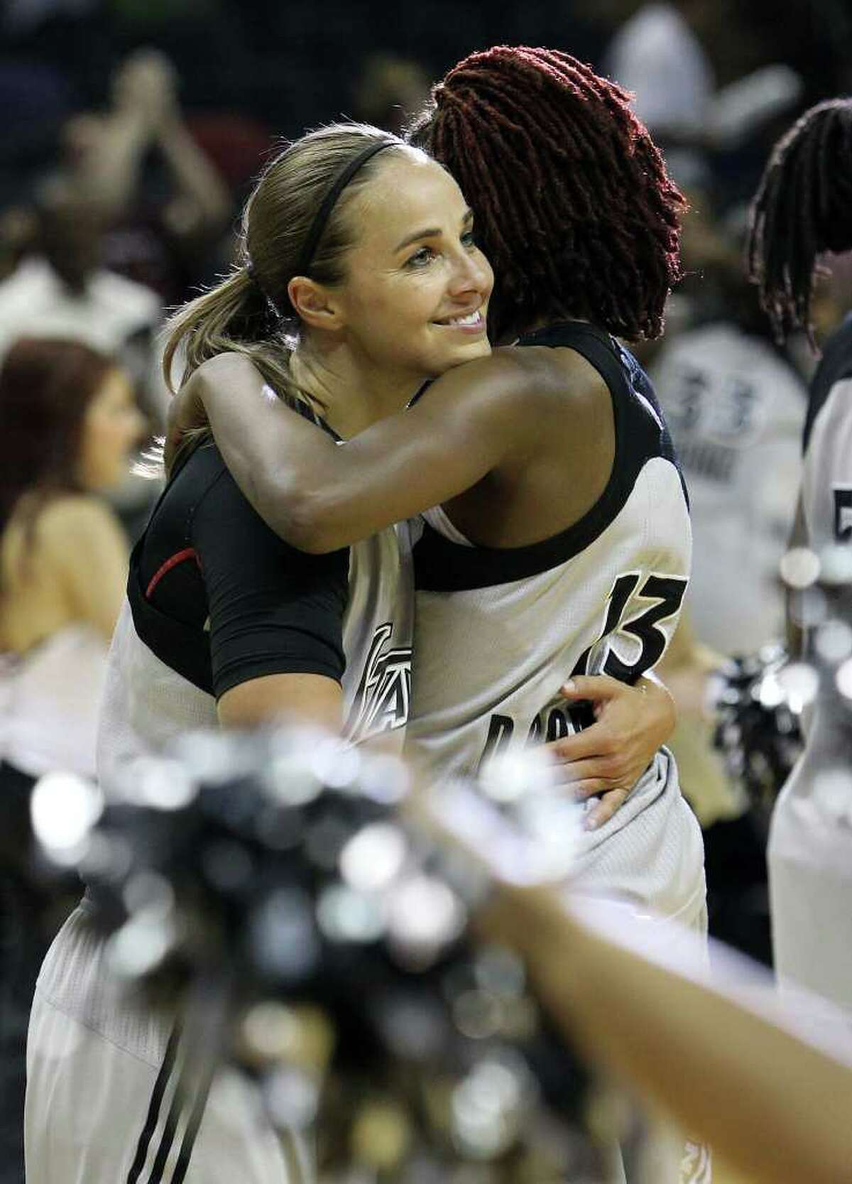 Silver Stars' Becky Hammon (25) gets a hug from teammate Danielle Robinson (13) after the Silver Stars defeated the Connecticut Sun, 78-66, at the AT&T Center on Tuesday, August 30, 2011. Hammon scored 16 points to surpass the 5,000 career point mark. Kin Man Hui/kmhui@express-news.net