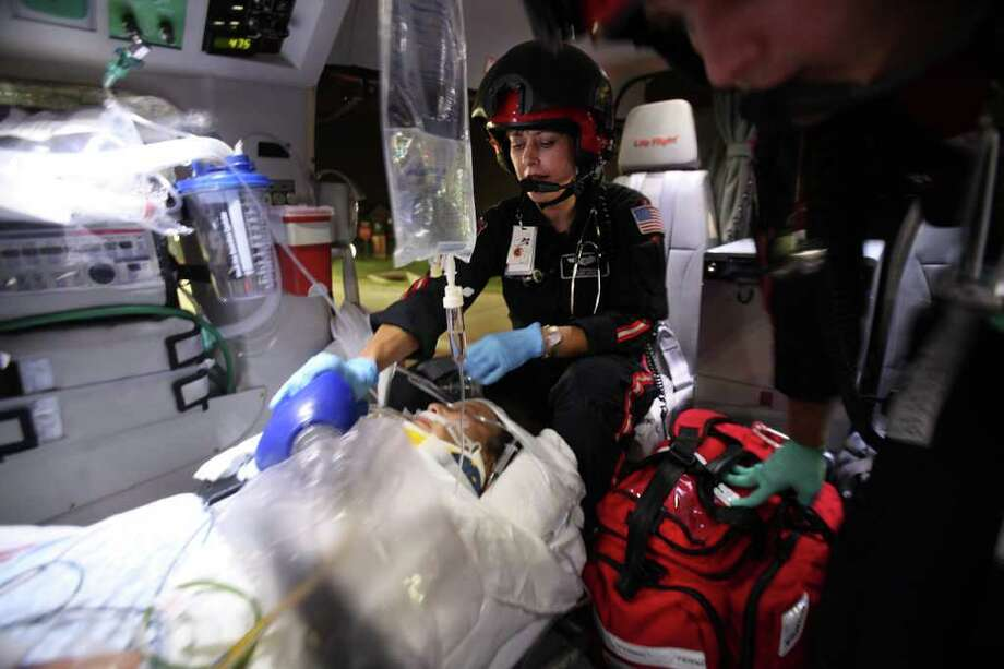 Lisa Covington, 44, a Life Flight RN and paramedic, and Ryan Price, 22, Life Flight Paramedic, continue to render medical aid to a critical patient on Life Flight bound toward the Memorial Hermann Hospital in the Medical Center on Friday, Aug. 19, 2011, in Houston. Photo: Mayra Beltran, Chronicle / © 2011 Houston Chronicle