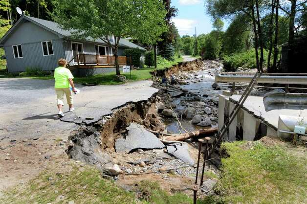 Resident Melissa Wells walks to her home, on left, alongside the Gulf Brook on Tuesday, Aug. 30, 2011, in Keene, N.Y. The brook took out the bridge and Wells' front yard. (Cindy Schultz / Times Union) Photo: Cindy Schultz