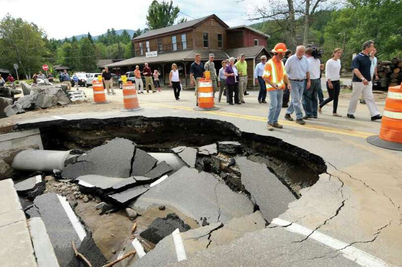 Officials and residents walk along a destroyed section of Route 9N on Tuesday, Aug. 30, 2011, in Kee