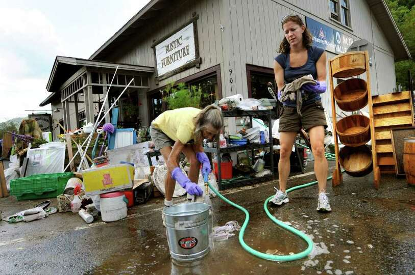 Residents Barbara Kausman, left, and Samantha Robinson help clean up the flooded general store on Tu