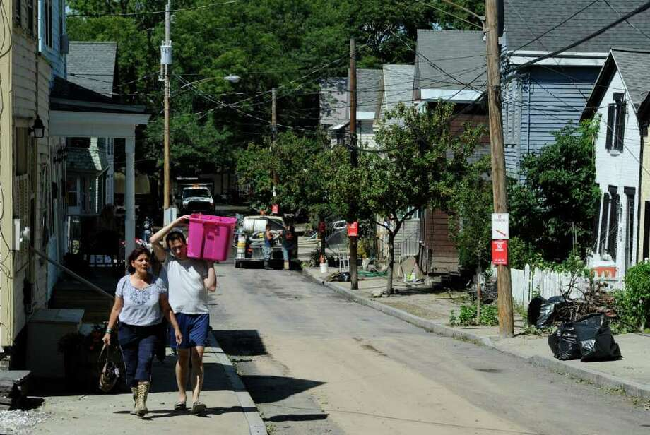 Residents carry belongings from their homes on N. Ferry Street Street in the Stockade section of Schenectady, N.Y. Aug 30, 2011.    (Skip Dickstein/ Times Union) Photo: Skip Dickstein / 00014452A