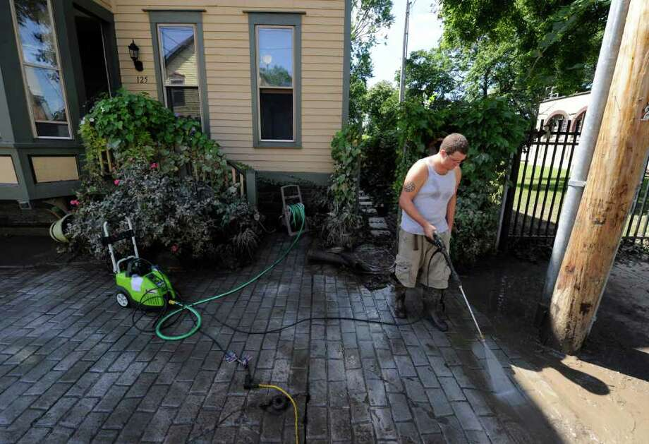 Clean up continues for volunteer Matt Volks in front of 110 North Street in the Stockade section of Schenectady, N.Y. Aug 30, 2011.    (Skip Dickstein/ Times Union) Photo: Skip Dickstein / 00014452A