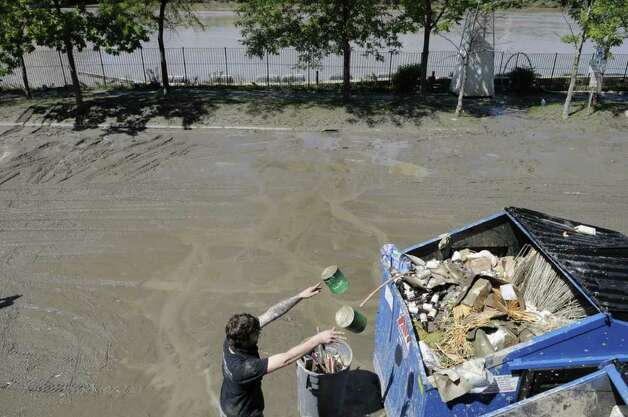 A employee of Brown's Brewing Company tosses canned food damaged by flood waters into a garbage bin in the parking lot  as cleanup from the Hudson River flooding took place on Tuesday, Aug. 30, 2011. (Paul Buckowski / Times Union) Photo: Paul Buckowski  / 00014452A