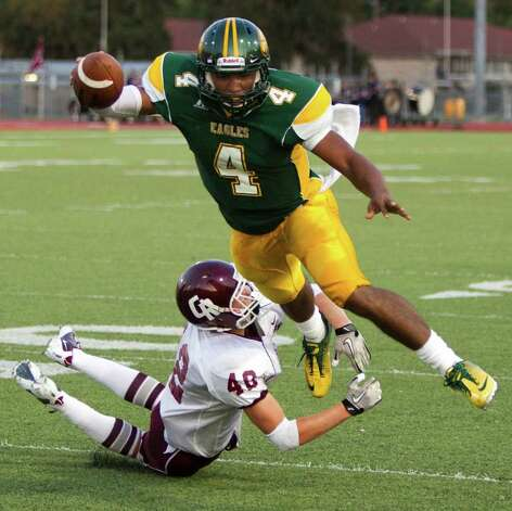 Klein Forest quarterback Matt Davis (4) dives out of the grasp of Cinco Ranch defensive back Kevin Colpoys (42) for a 10-yard touchdown run during the second quarter of a Class 5A non-district high school football game at Klein Memorial Stadium Thursday, Aug. 25, 2011, in Houston. Photo: Brett Coomer, Houston Chronicle / © 2011 Houston Chronicle
