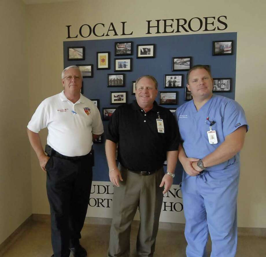 """Mike Legoudes (Humble EMS Asst Fire Chief) David Beck (Memorial Hermann NE Emergency Dept Director) and James Rinkle (M.D. Emergency Medicine) in front of the """"Local Heroes"""" wall of photos of a few of the ambulance personnel who have brought patients to the emergency room of Memorial Hermann Northeast Friday 8/19/11. Photo by Tony Bullard. Photo: Tony Bullard / Credit: for the Chronicle"""