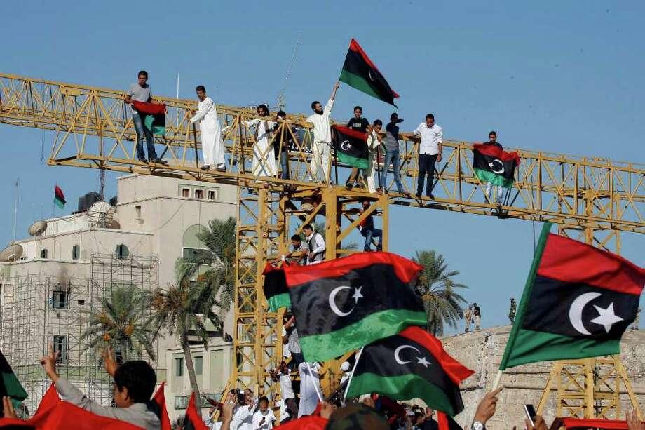 Libios festejan con banderas de su país en la Plaza Verde, rebautizada Plaza de los Mártires, mientras celebran el final del Ramadan y su victoria sobre las tropas leales a Moammar Gadhafi, enTrípoli, Libia, el miércoles 31 de agosto de 2011. Photo: Francois Mori, STF / AP
