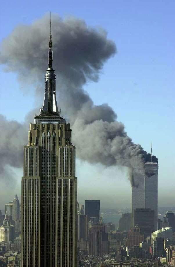 FILE - In this Sept. 11, 2001, file photo, plumes of smoke rise from the World Trade Center buildings in New York. The Empire State building is seen in the foreground. Television viewers who want to immerse themselves in memories of the Sept. 11 terrorist attacks as the 10th anniversary approaches will have a staggering number of choices, and on the day itself, broadcast and cable news networks will all have their top talent on hand for special coverage. (AP Photo/Patrick Sison, File) Photo: Patrick Sison