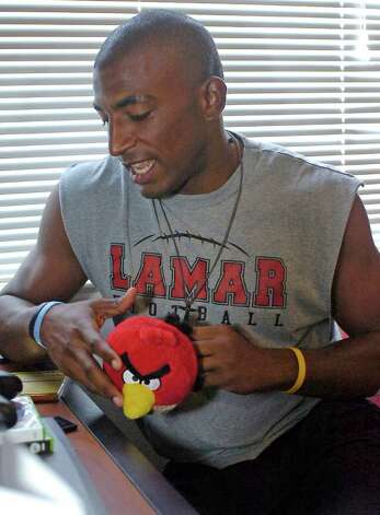 J.J. Hayes is now a Lamar University football player who lived briefly in a Chevy van while he was a student at Diboll High School. This is where Lamar University Head Football Coach Ray Woodard found him the day he went to sign him to play for Lamar.   He now lives in a dormitory at Lamar University and loves to play video games and listen to music in his free time.  Taking a break from one of his games, he searches for another song while holding a prized possession, a stuffed Cardinal known as Seymour.  Dave Ryan/The Enterprise Photo: Dave Ryan