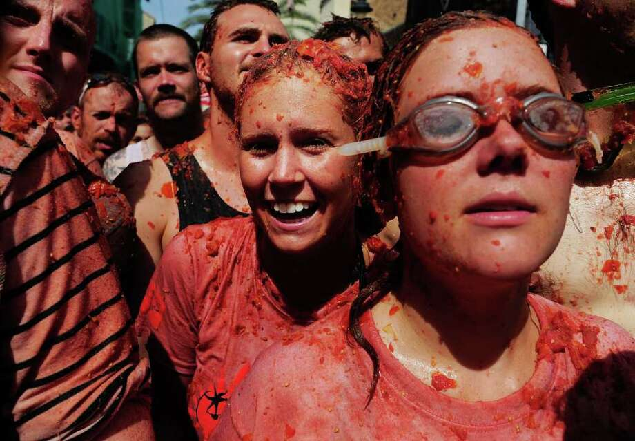 Revelers are covered in tomato juice while participating in the annual Tomatina on Wednesday in Bunol, Spain. An estimated 35,000 people threw 120 tons of ripe tomatoes in the world's biggest tomato fight held annually in this Spanish Mediterranean town. Photo: Denis Doyle, Getty Images / 2011 Getty Images