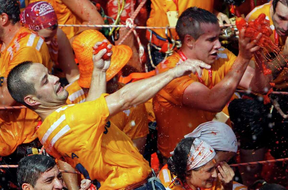 Revelers throw tomatoes during the annual