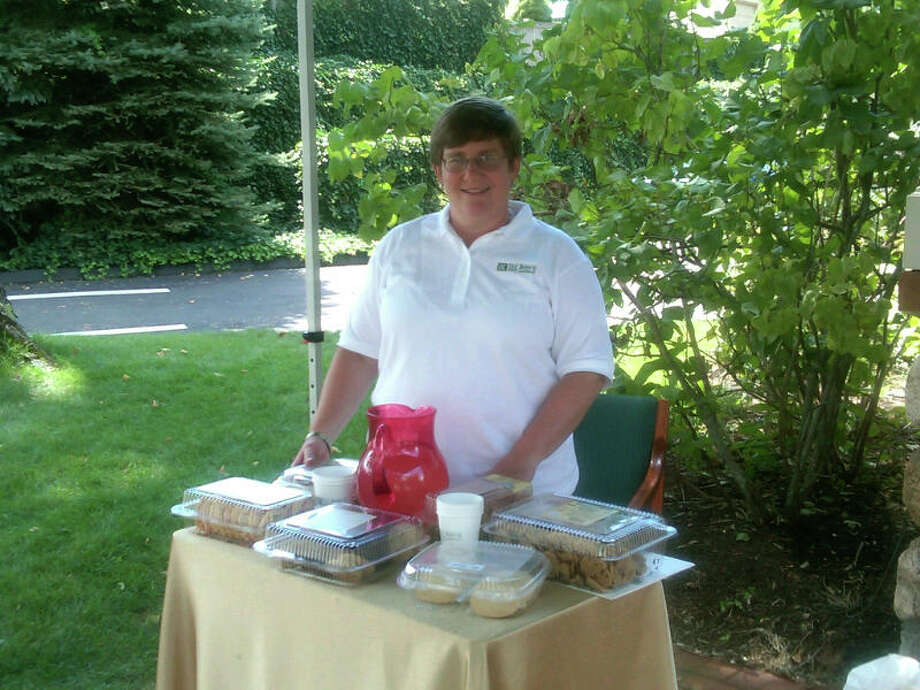 Stacey Lambert, a commercial loan officer for the Bank of New Canaan, stands outside the Cherry Street Branch with cookies and lemonade for customers. The Elm Street branch is closed because it has no power. The bank will have cookies until 4 p.m. Photo: Belinda Stasiukiewicz