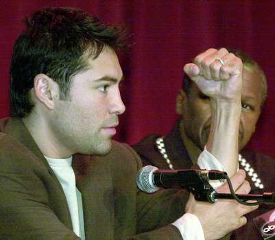 Oscar De La Hoya, left, demonstrates the power of his left wrist as his trainer, Floyd Mayweather Sr., right, looks on during a news conference Wednesday, May 22, 2002, in Los Angeles. De La Hoya recently underwent surgery for a torn ligament in his left wrist, an injury he sustained while training this past spring. The injury caused De La Hoya to reschedule his fight against Fernando Vargas for Sept. 14, 2002, in Las Vegas. (AP Photo/Krista Niles) Photo: KRISTA NILES, Associated Press / AP