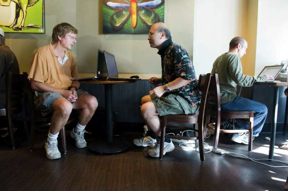 Eric Bernhard and Addison Cheng share a table at the Starbucks at Ridgeway which drew people seeking internet connections and cold drinks in Stamford, Conn., August 29, 2011, after power was knocked out throughout much of the city by Hurricane Irene. Many businesses suffered lost revenue when they were not able to open for business for days due to the power outages, many professionals relied on public venues for connections to their work place and the ability to work. Photo: Keelin Daly / Stamford Advocate