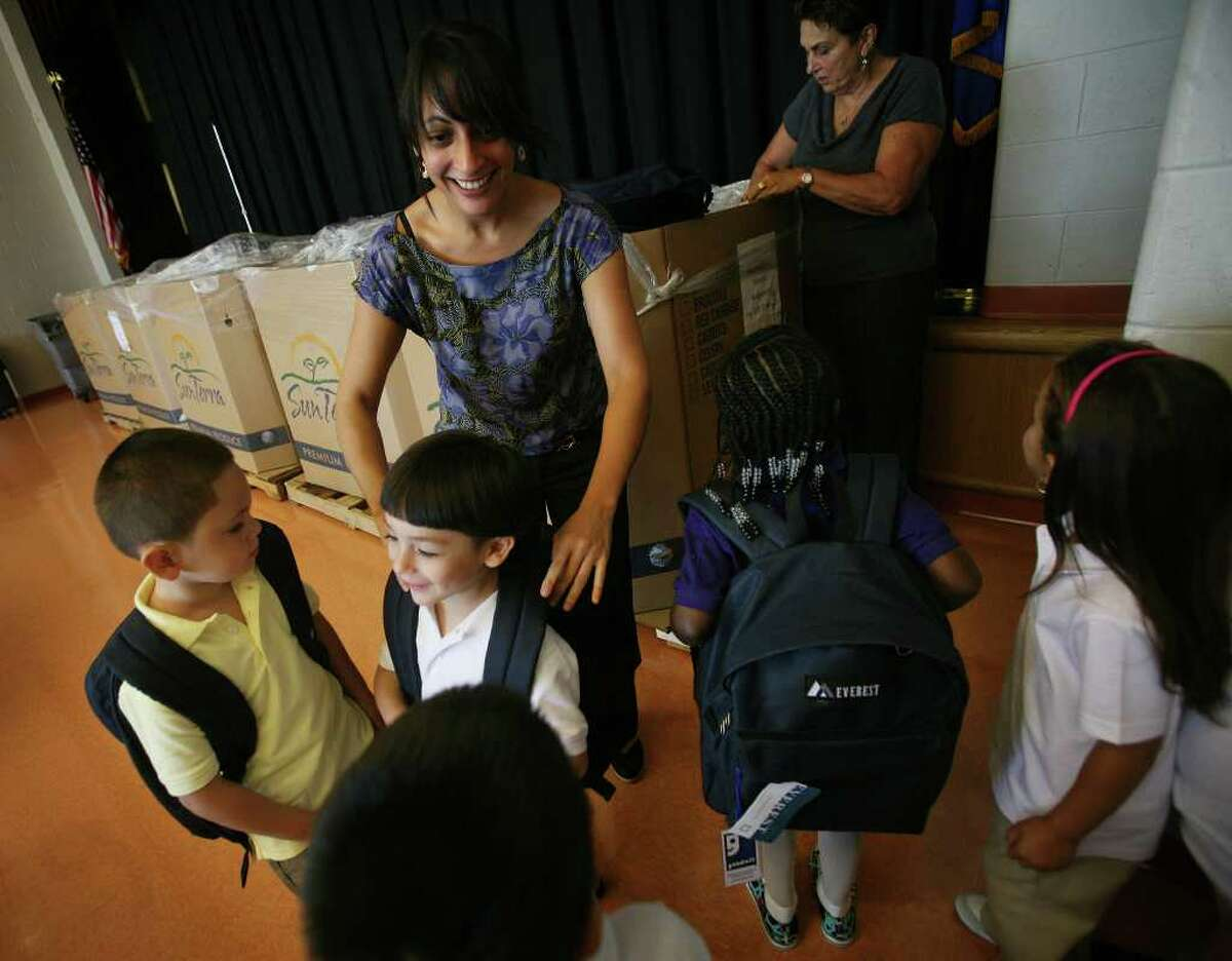 On the first day of school in Bridgeport, kindergarten teacher Angela Baldino passes out new bookbags filled with school supplies to her students at Waltersville School on Wednesday, August 31, 2011.