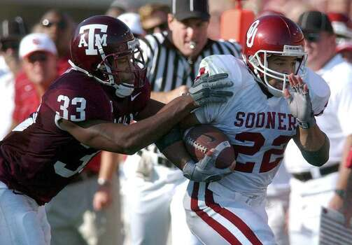 Despite rushing for 141 yards, Oklahoma's Quentin Griffin (22) was held in check by Texas A&M defenders like Oschlor Flemming (33) as the Aggies went on to win 30-26 at Kyle Field Stadium on Saturday, November 9, 2002. Photo: KIN MAN HUI, SAEN / SAN ANTONIO EXPRESS-NEWS