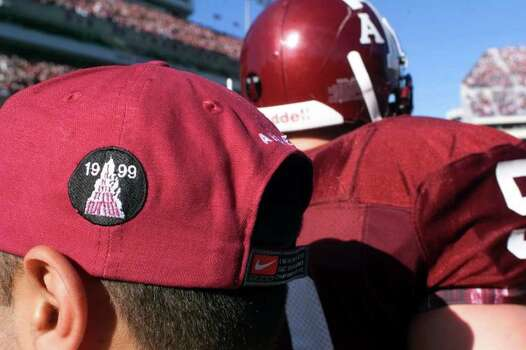 Texas A&M student Steve Rophail, a student trainer, wears a patch on his hat symbolizing the bonfire tragedy. Players also wore a sticker on the back of their helmets. The Aggies defeated No. 5 Texas 20-16 a week after the bonfire collapsed and killed 12 Aggies. Photo: DOUG SEHRES, SAEN