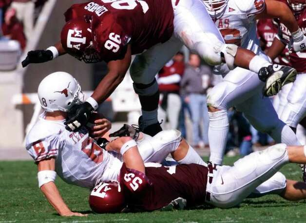 Texas A&M defenders Chad Frantzen (59) bottom and Ron Edwards (96) sandwich Texas QB Chris Simms during a fourth period sack during the Aggies 20-16 win at Kyle Field Nov. 26, 1999. Photo: DOUG SEHRES, SAEN