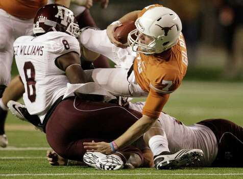 Texas Longhorns quarterback Garrett Gilbert (7) is sacked by Texas A&M Aggies linebacker Garrick Williams (8) during the second half of the University of Texas-Texans A&M college football game at Texas Memorial Stadium, Nov. 25, 2010, in Ausitn. Texas A&M won the game 24-17. Photo: SAEN