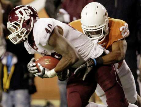 In this Nov. 25, 2010 photo, Texas A&M's Von Miller (40) pulls down an interception as Texas' Fozzy Whittaker (28) stops him during the fourth quarter of an NCAA college football game in Austin, Texas. The Aggies won 24-17. Photo: SAEN