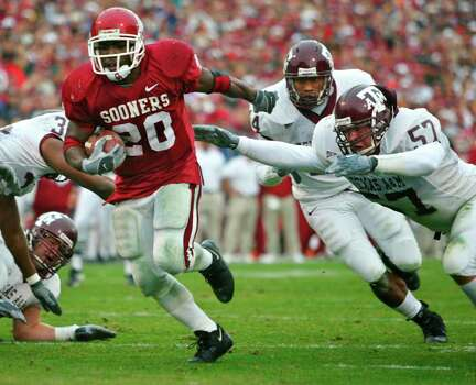 Oklahoma running back Kejuan Jones, left, avoids a last ditch attempt at a tackle by Texas A&M defender Scott Stickane, right, for a touchdown in the first quarter of the game in Norman, Okla., Saturday, Nov. 8, 2003. The Aggies lost 77-0. Photo: SUE OGROCKI, SAEN / AP