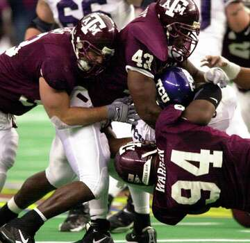 Texas A&M defenders Evan Perroni (93), Jarrod Penright (43) and Ty Warren (94) team up to bring down TCU quarterback Casey Printers (1) during the Gallery Furniture.Com Bowl Friday, December 28, 2001 at the Astrodome. The Aggies won 28-9. Photo: BAHRAM MARK SOBHANI, SAEN
