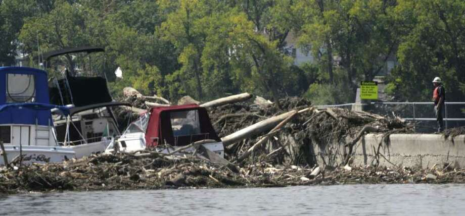 Boats that broke loose and debris fill in around the Federal Lock at the Troy dam in Troy on Wednesday, Aug. 31, 2011.  Crews were working to remove the debris from the water and the lock walls. (Paul Buckowski / Times Union) Photo: Paul Buckowski  / 00014477A