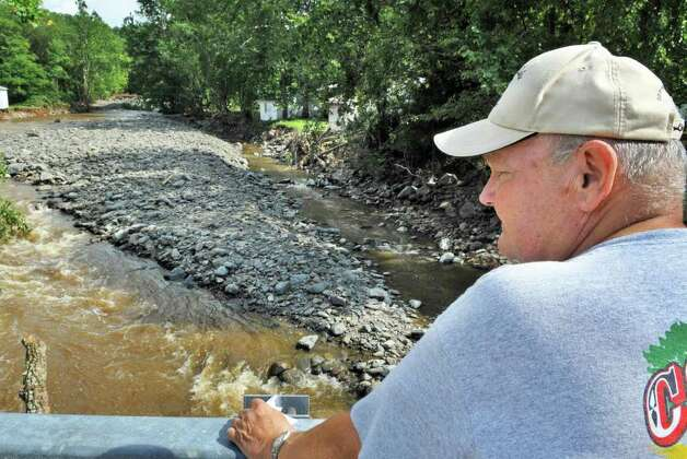 Poestenkill resident Al Horton looks down at the Poesten Kill   in Poestenkill on Wednesday Aug. 31, 2011.  This weekend's flooding created a new creek channel, at left. (John Carl D'Annibale / Times Union) Photo: John Carl D'Annibale