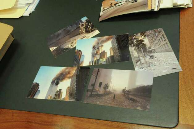 Photographs show the events of Sept. 11 lay on a desk in the Greenwich office of Michael Freeburg, a survivor of the terrorist attacks.  Freeburg worked as a trader in the World Financial Center at the time of the attacks. Photo: Helen Neafsey / Greenwich Time