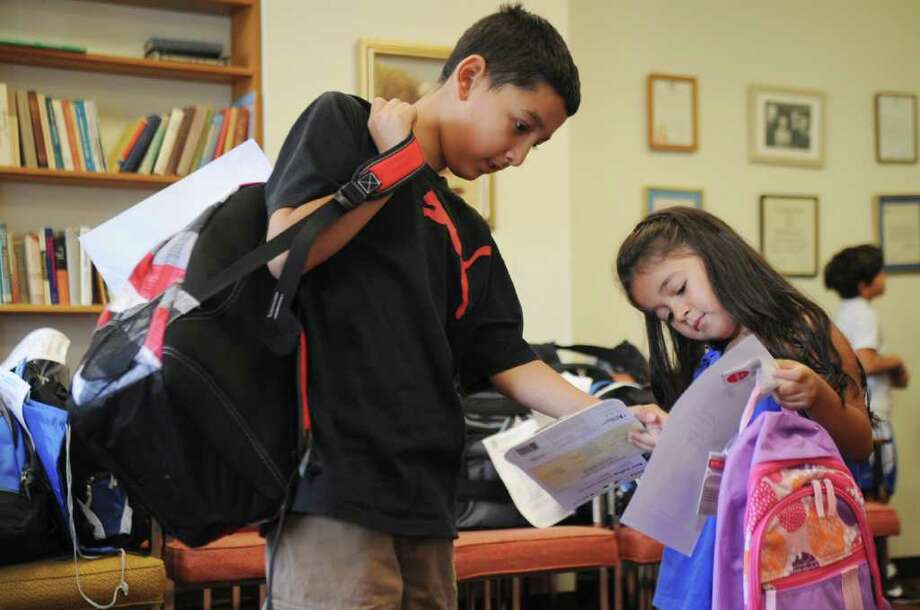 Anthony Perez, 11, and his sister Fernanda, 5, check out school supplies at Greenwich Town Hall on Wednesday, Aug. 31, 2011. The Greenwich Rotary Club and Greenwich social services distributed school supplies to 195 childeren from low-income families Wednesday. Photo: Helen Neafsey / Greenwich Time
