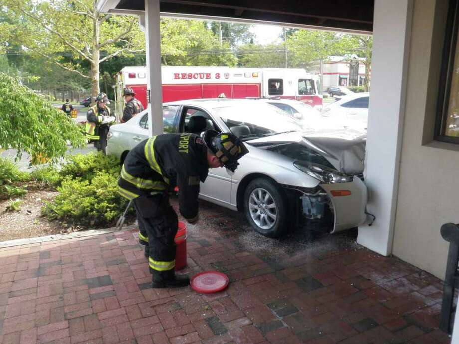 A Lexus plowed into the front of Country Curtains on Post Road East Wednesday afternoon, but the driver escaped serious injury and the building was not damaged. Photo: Westport Fire Department / Westport News contributed