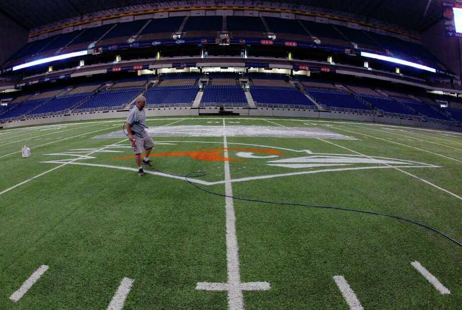 Alamodome facility operations coordinator Tom McAfee applies the first color of paint onto the UTSA logo on the football field at the Alamodome on Wednesday, August 31, 2011. About 25 gallons of paint will be used to paint the logos at mid-field and in the end zones according to Alamodome officials. McAfee has been the appointed artist at the Alamodome for the past 20 years. UTSA will play their first football game on Saturday. Kin Man Hui/kmhui@express-news.net Photo: KIN MAN HUI, -- / SAN ANTONIO EXPRESS-NEWS (NFS)