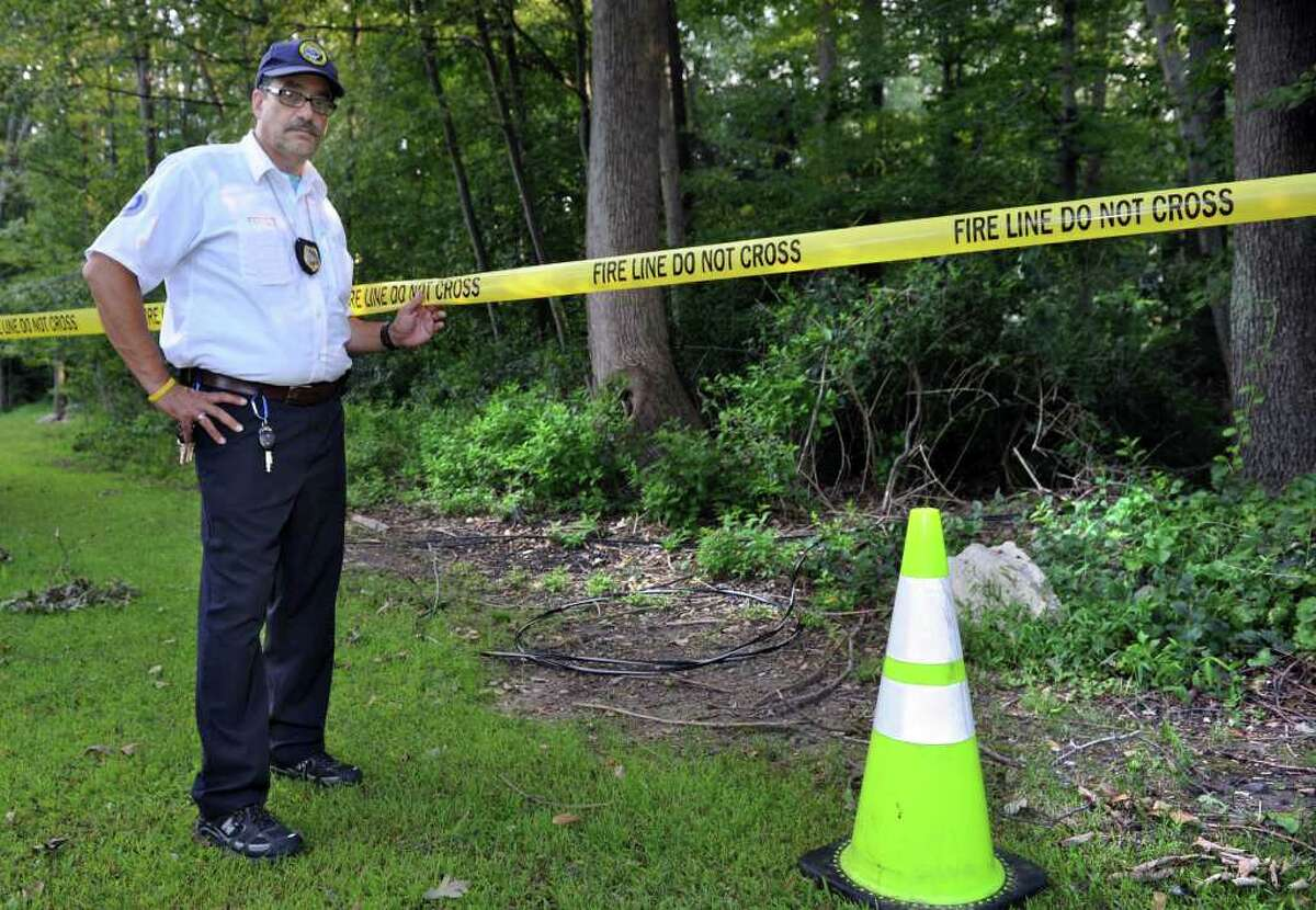Dallas Toto stands near downed electrical wires on his property on Oak Crest Drive in Brookfield. The wires came down during Tropical Storm Irene. Photo taken Wednesday, August 31, 2011.