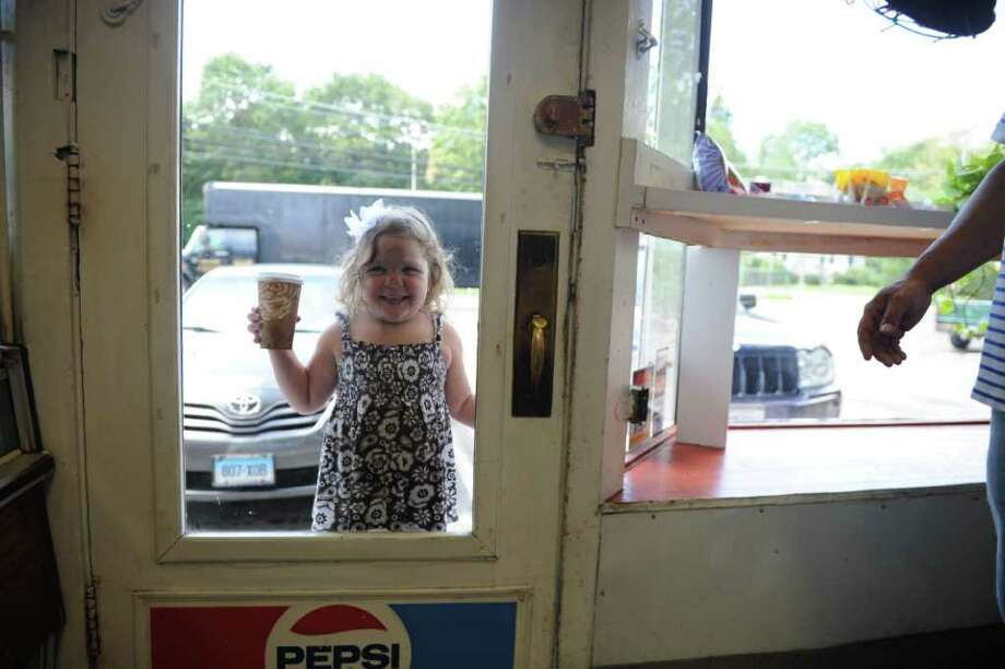 Alexandra Martinez, 4, presses her nose against the glass in the door of her grandparent's Pine Hill Deli, Grocery and Market which is closing after 34 years because the landlord is not renewing their lease for the High Ridge Road location in Stamford, Conn., August 31, 2011. The deli will open later this fall on Hope Street. Photo: Keelin Daly / Stamford Advocate