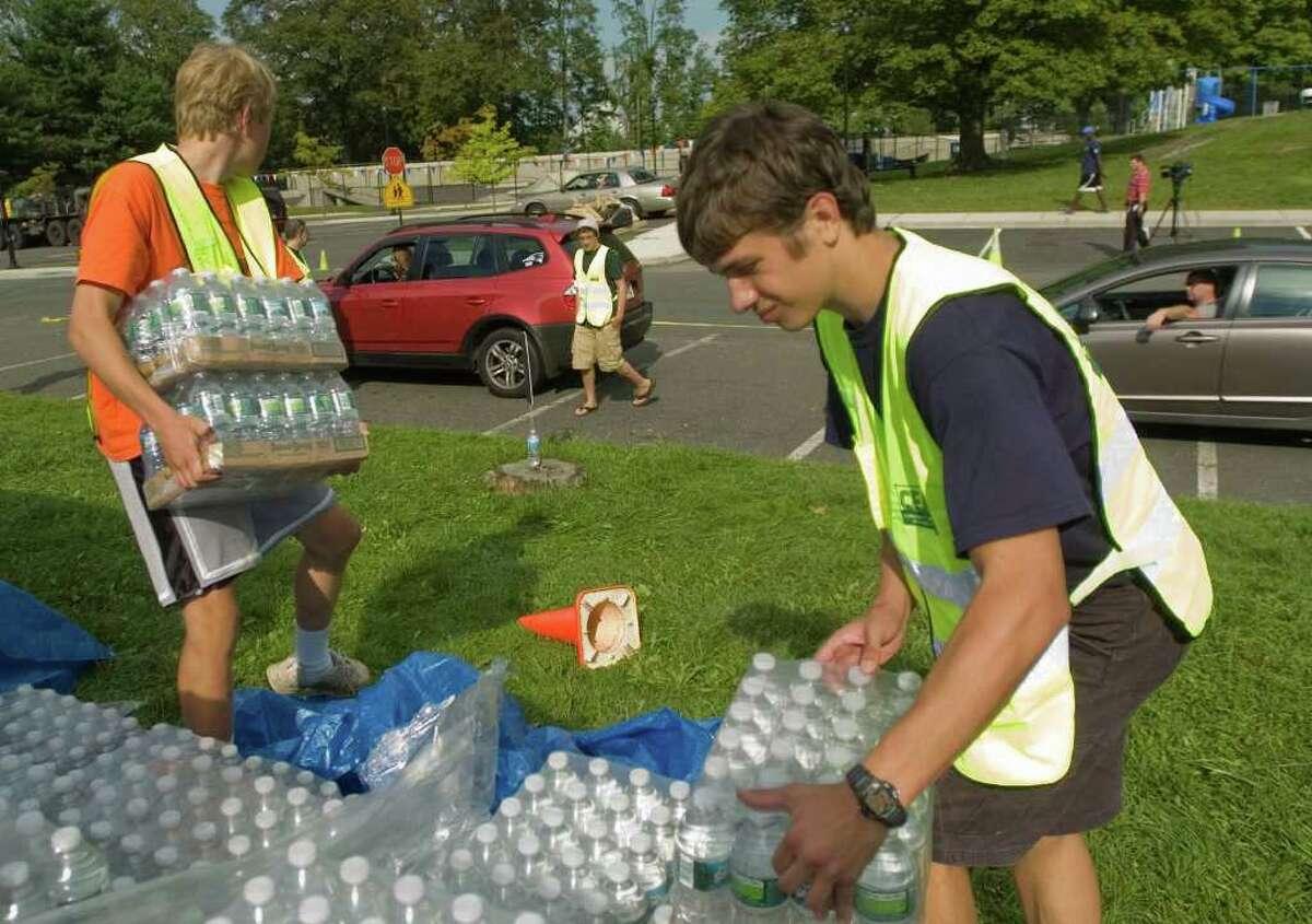 Volunteers from Ridgefield, Ryan Konopka, 15, left, and David Konopka, 17, haul 24-packs of water off pallets and into residents' vehicles outside Yanity Gym in Ridgefield on Wednesday, Aug. 31, 2011.